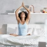 Young African American Woman Doing Yoga In Bed After Sleep